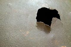 A hole with torn edges in a dark green steel surface. Close-up, shallow depth of field. royalty free stock photo