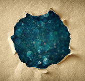 Hole through torn paper and dark blue boke lights background Stock Images