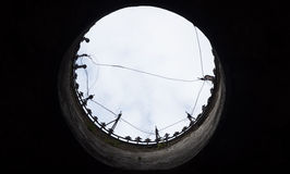 The hole. A hole with a view to the contrary to the outside with cloudy sky and wires that are intertwined Royalty Free Stock Image