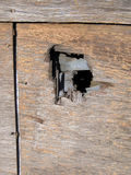Hole in the Wall. A hole in a weathered old plywood wall Royalty Free Stock Image