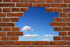 Hole in the wall. Blue sky seen through a hole made in the brickwall Royalty Free Stock Image