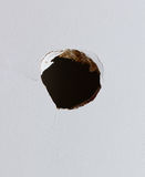 Hole in the wall. Hole punched into a cabinet or wall Royalty Free Stock Image