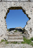 Hole in the wall of an ancient Spanish ruin. Dark blue sky as seen through a hole in the wall of an ancient Spanish ruin, with steps that lead to nowhere but a stock image
