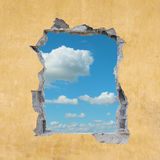 Hole in Wall. A Hole in a Wall with Blue Sky Stock Photo