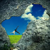 Hole in the Wall. Into Nature Landscape with Somersault of Teenage Boy Stock Photo