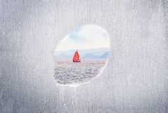 A hole in a wall with sailing boat on the calm sea. Concept restricted area, freedom. Copy space. Hole in a wall with sailing boat on the calm sea. Concept royalty free stock image