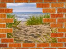 Hole in the Wall to the Ocean. Brick wall background in various shades of red, orange, and gray with a hole leading from urban to a beach path to the ocean Stock Photography