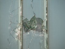 Hole in a window. Made by vandalism Royalty Free Stock Image