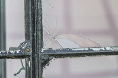 A hole in the window pane. A broken pane of glass - by bullet drilled through royalty free stock image