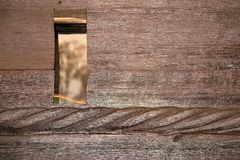 Hole in wooden wall. Closeup of wooden wall with small opening or window Stock Photography