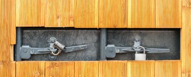 Hole in a wooden wall with two padlocks on a grey metallic door. Square hole in a wooden wall with two small padlocks on a grey metallic door. Close up Stock Photos