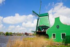 Holenderów zieleni wiatraczki nad rzeką Fotografia Royalty Free