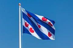 Holenderska Fryzyjska flaga przeciw jasnemu niebieskiemu niebu Zdjęcie Royalty Free
