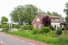 Holenderski dom na wsi z ogródem, kanałem i mostem, holandie obrazy stock