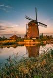 Holenderski wiatraczek wzdłuż rzeki podczas złotej godziny fotografia royalty free