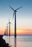 Holenderskiego rzędu na morzu silniki wiatrowi przy pięknym zmierzchem Zdjęcia Royalty Free