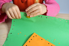 Holes. Little girl make holes in sheets of paper Royalty Free Stock Photography