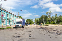 Holes and cracks in the asphalt country road in the small russian village Stock Photo
