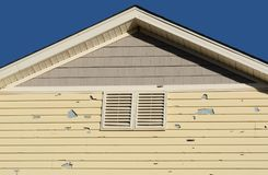 Home Hail damage. Holes in exterior siding in home from damage by hail storm royalty free stock photography