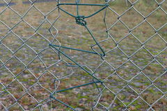 Holes in the fence. Broken wire fence. patched up Stock Photo