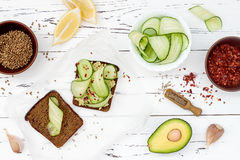 Holewheat toast with avocado guacamole and cucumber slices. Breakfast with spicy avocado sandwiches on whole grain bread. Royalty Free Stock Images