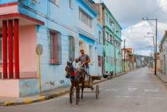 Holguin, Куба: Местные кубинцы снаружи на жилой улице Кубинец местного жителя едет в тележке с лошадью стоковая фотография rf