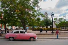 Holguin, Cuba : la rétro vieille voiture rose a garé sur une rue au centre de la ville Cathédrale dans Holguin du centre Photographie stock libre de droits