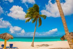 Holguin, Cuba, Playa Esmeralda. Beautiful Caribbean sea turquoise blue color and palm trees on the beach. Sun loungers and umbrell. As for tourists stock photos