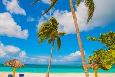 Holguin, Cuba, Playa Esmeralda. Beautiful Caribbean sea turquoise blue color and palm trees on the beach. Sun loungers and umbrell. As for tourists. Paradise stock image