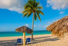 Holguin, Cuba, Playa Esmeralda. Umbrella and two lounge chairs around palm trees. Tropical beach on the Caribbean sea. Holguin, Cuba, Playa Esmeralda. Umbrella royalty free stock image