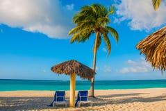 Holguin, Cuba, Playa Esmeralda. Umbrella and two lounge chairs around palm trees. Tropical beach on the Caribbean sea. Stock Photos