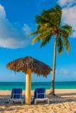 Holguin, Cuba, Playa Esmeralda. Umbrella and two lounge chairs around palm trees. Tropical beach on the Caribbean sea. Holguin, Cuba, Playa Esmeralda. Umbrella Stock Photography