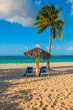 Holguin, Cuba, Playa Esmeralda. Umbrella and two lounge chairs around palm trees. Tropical beach on the Caribbean sea. Paradise landscape stock photography