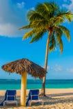 Holguin, Cuba, Playa Esmeralda. Umbrella and two lounge chairs around palm trees. Tropical beach on the Caribbean sea. Royalty Free Stock Photo