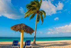 Holguin, Cuba, Playa Esmeralda. Umbrella and two lounge chairs around palm trees. Tropical beach on the Caribbean sea. Paradise la Royalty Free Stock Photography