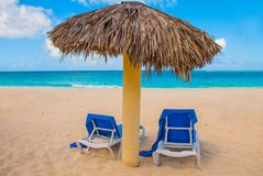 Holguin, Cuba, Playa Esmeralda. Umbrella and two sun loungers are on the sand. Tropical and Paradise beach on the Caribbean sea. Holguin, Cuba, Playa Esmeralda royalty free stock images