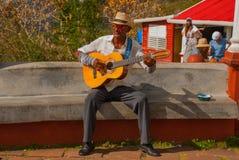 HOLGUIN KUBA: Hög man med gitarren som bär en traditionell Panama sugrörhatt som busking i en gata arkivbild