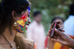 Holi celebration. Woman viewing her painted face on a mobile phone while enjoying holi festival in India Royalty Free Stock Photo