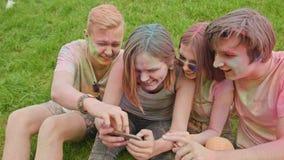 Holi festival celebrants watching photos on phone