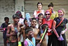 Holi Festival in India. March 09, 2012  Kolkata, West Bengal, India - Street children celebrating holi festival with foreign travelers at Kolkata Stock Photo