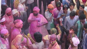 Holi festival in india. Barsana, Mathura District, Uttar Pradesh, India - 03/25/2013 - Pan shot of people celebrating and dancing in colorful Holi festival with stock footage