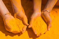 Holi hands. Couple of hands holding orange holi paint Stock Image
