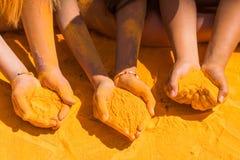 Holi hands. Couple of hands holding orange holi paint Stock Images