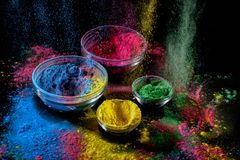 Holi paint background. Several bowls with different color powder inside. Color powder explosion on black. stock images