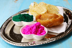 Holi platter. A platter decorated with Holi food and color includng, Gujiya and potato chips stock image