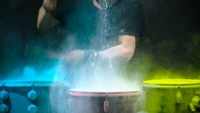 Holi powder bounces off the drum in the form of a shock wave, Close up. Black background