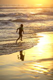 Holiday. Young boy running on the beach at sunset Stock Photography