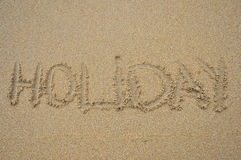 Holiday. Word written in the sand on the beach Stock Photography
