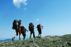Holiday. Four people going up in mountain Royalty Free Stock Image
