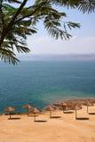 Holiday. On the seashore with sandy beach and umbrellas (Dead Sea coast, Jordan Stock Photography